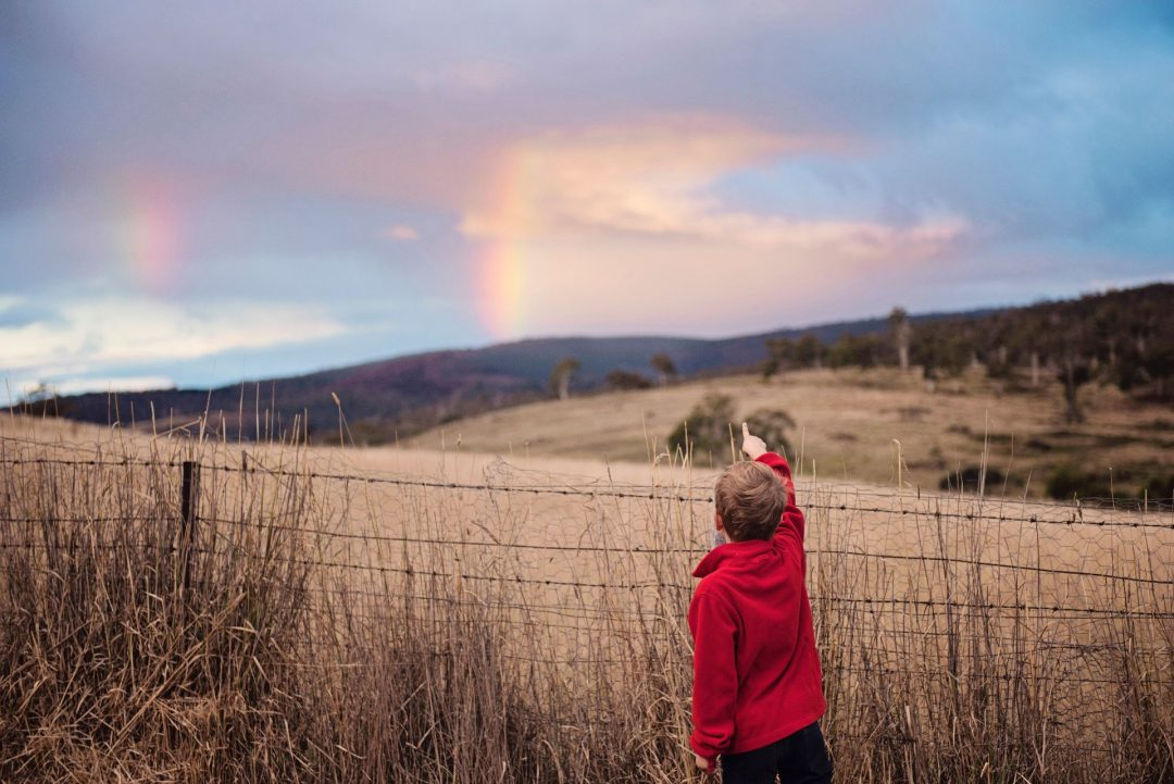 A boy of around 10 years old points at a rainbow and interesting cloud formation in the sky. He is standing in a hilly field with dry grass and a barbed wire fence.