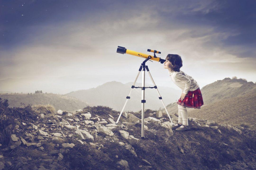 Girl looking through a telescope