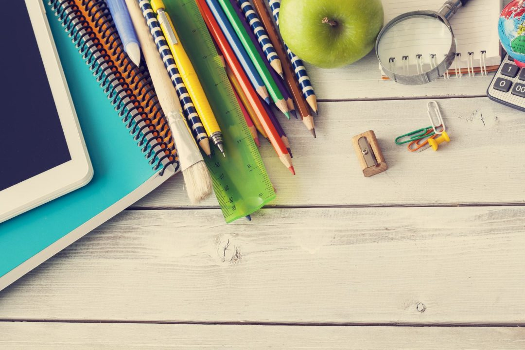 Collection of teacher supplies and stationery on a desk