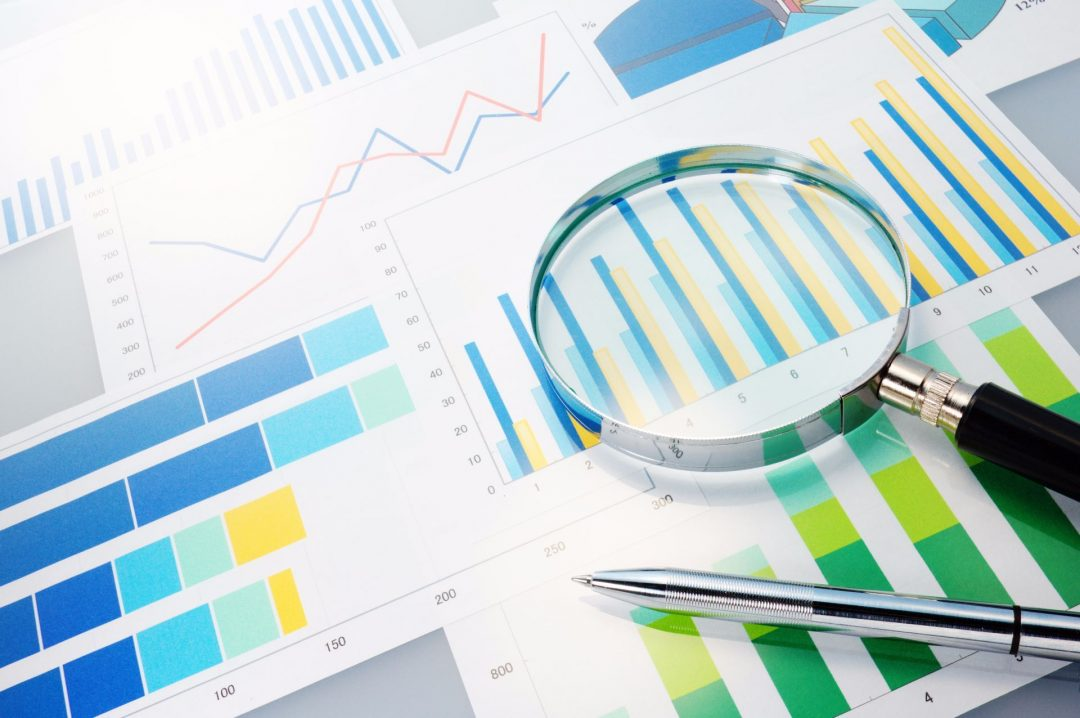 Magnifying glass lying on print outs of graphs and charts